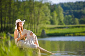 Long red hair romantic woman relax by lake with book — Stock Photo