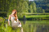Long red hair romantic woman relax by lake — Stock Photo