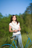 Woman with old-fashioned bike in summer meadow — Stock Photo