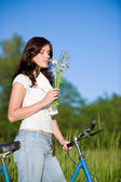 Woman with old-fashioned bike and summer flower — Stock Photo