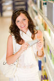 Shopping cosmetics - smiling woman with moisturizer — Stock Photo