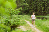 Sportive man jogging in nature by lake — Stock Photo