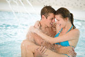 Swimming pool - young loving couple have fun — Stock Photo