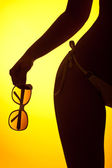 Silhouette of female body with bikini and sunglasses — Stock Photo