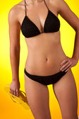 Part of female body wearing black bikini and holding yellow fli — Stock Photo