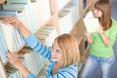 Studente in biblioteca - donna due scegliere libro — Foto Stock