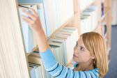 Student in library - happy woman reach for book — Stock Photo