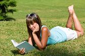Smiling young woman lying down on grass with book — Stock Photo