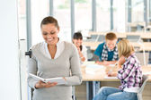 Female teacher with book and students in classroom — Stock Photo