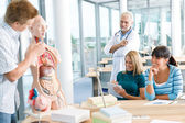 Medical students with professor and human anatomical model — Stock Photo