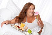 Young woman having breakfast in bed — Stock Photo
