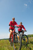 Young couple riding mountain bike in spring meadow — Stok fotoğraf