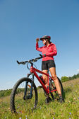 Young woman with mountain bike in spring nature — Stock Photo