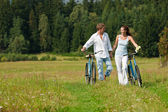 Romantic young couple with old bike in spring nature — Stok fotoğraf