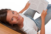 Brown hair teenager lying down holding book — Stock Photo
