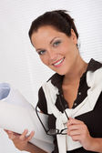 Smiling female architect with plans — Stock Photo