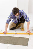 Home tile improvement - handyman with level — Stock Photo