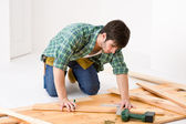 Home improvement - handyman installing wooden floor — Stock Photo