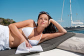 Attractive woman sunbathing on luxury boat — Stock Photo