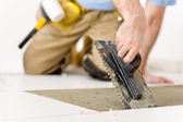 Het huisverbetering, renovatie - klusjesman houdende van tegel — Stockfoto