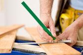Home improvement - close-up of handyman measure wood — Stock Photo