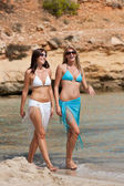 Two attractive woman walking on the beach — Stock Photo