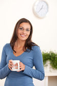 Happy young woman holding cup of coffee — Stock Photo
