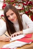 Jovem mulher pensar ao escrever o cartão de natal — Foto Stock