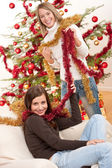 Two smiling women with Christmas chains — Foto Stock
