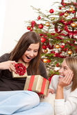 Due donne sorridente spacchettamento regalo di natale — Foto Stock