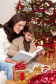 年轻的母亲和儿子在圣诞节上读的书 — 图库照片
