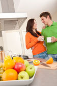 Happy couple drinking coffee in the kitchen — Stock Photo