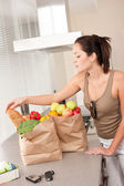 Young woman with groceries in the kitchen — Stock Photo