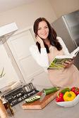 Souriant cookbook de tenue de femme dans la cuisine — Photo