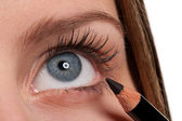 Blue eye, woman applying black make-up pencil — Stock Photo