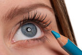 Blue eye, woman applying turqouise make-up pencil — Stock Photo