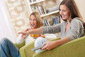 Students - Two smiling female teenager watching television — Stock Photo