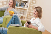 Students - Two smiling female teenager watching television toget — Stock Photo