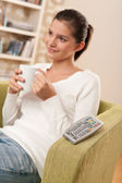 Students - Happy female teenager watching TV — Stock Photo