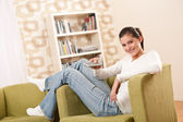 Students - Smiling female teenager watching television — Stock Photo