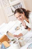 Jonge vrouwelijke interieur ontwerper op kantoor met verf — Stockfoto