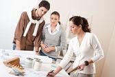 Weibliche innenarchitekt mit zwei kunden im büro — Stockfoto