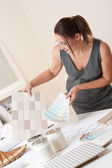 Female interior designer working at office with color swatch — Stock Photo