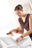 Smiling female designer with color swatch and laptop — Stock Photo