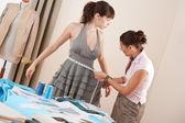 Female fashion designer measuring model for fitting — Stock Photo