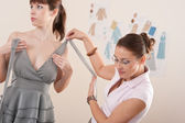 Female fashion designer pinning gray dress on model — Stock Photo