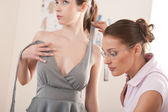 Female fashion designer pinning dress on model — Stock Photo