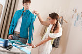 Female fashion designer measuring jacket on model — Foto Stock