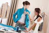 Model fitting by female fashion designer — Stock Photo