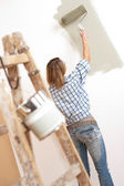 Home improvement: Cheerful woman with paint roller and ladder — Stock Photo